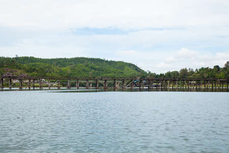 Wooden bridge across the river. The mountain in the back and on both sides of the river. photo