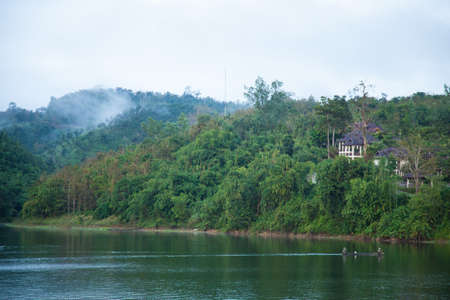 resort is on the mountain. Trapped near the river. Mountains with dense tree cover. photo