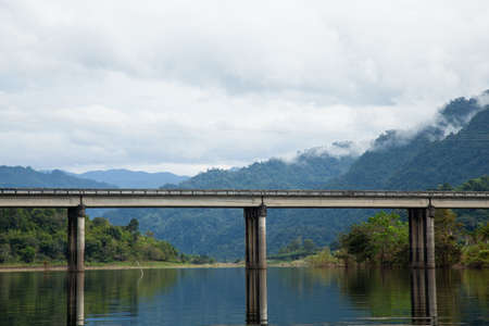 Bridge across the river. The mist covered mountains in the background. photo