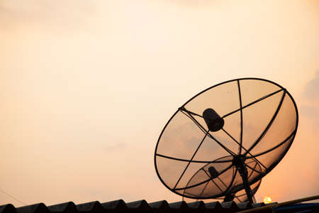 Satellite TV receiver. Mounted on the roof. In the evening. photo