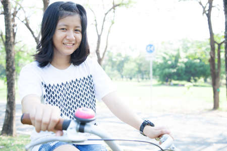 Young woman bicycling. Within the park. The space allocated for bicycling in particular.