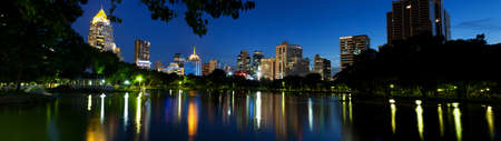 panorama bangkok city at night.Building a pond in front of the park. photo