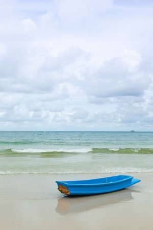 blue boat on sand beach.Half the sky, and a little wave. photo