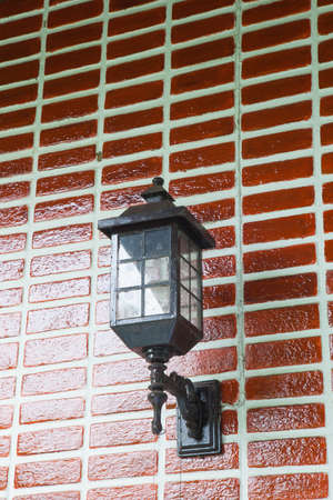 Lamp on the wall. Home painted red brick wall with black lamp. photo