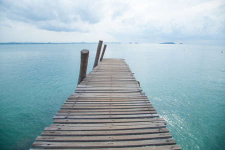 Wooden bridge into the sea. Overcast sky like a storm is coming.