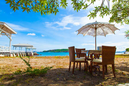 Chairs and table under umbrella Near the sea At the bright air. On of Weekend. photo
