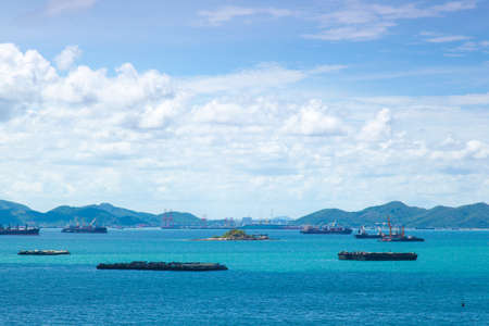 Cargo ships. Moored in the sea near the island. The bright sky in the daytime. photo