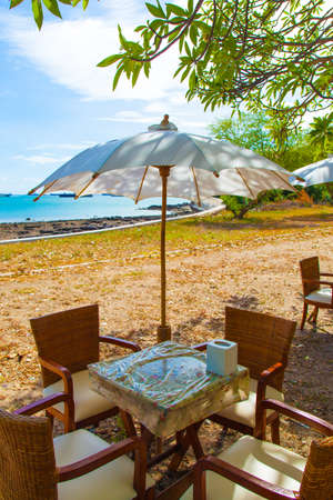 Dining Table and umbrella. Under a tree in a seaside restaurant. Cloudy atmosphere. photo