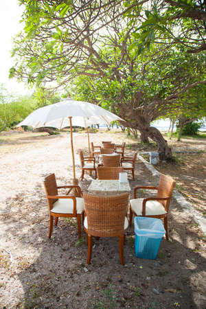 Dining Table and umbrella. Under a tree in a seaside restaurant. Cloudy atmosphere. Stock Photo - 23041007
