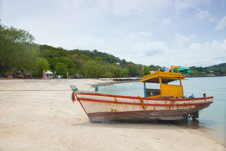 Small fishing boat. Parked on the beach. Ships were made of wood. photo