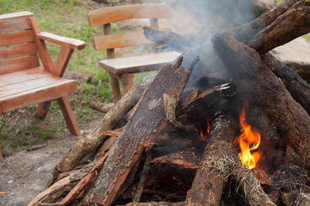 sit around: Fire burning Use of wood as fuel There are chairs to sit around the campfire