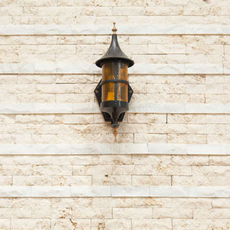 Lamp on the wall Black lantern on the wall made of small bricks. photo