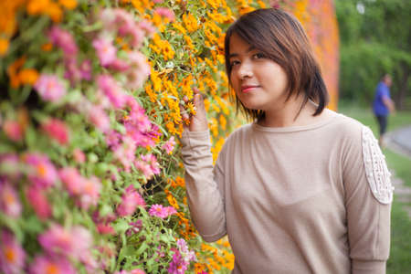 Portrait Asian woman standing near yellow flowers. Within the park area With small yellow flowers photo