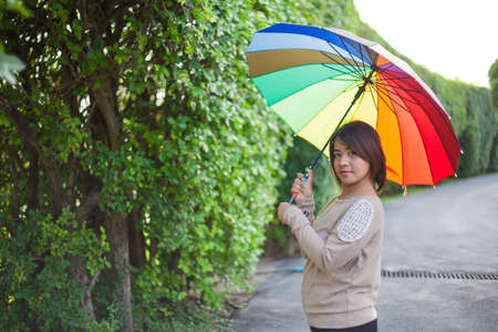Asian woman holding an umbrella on the sidewalk. The Park photo