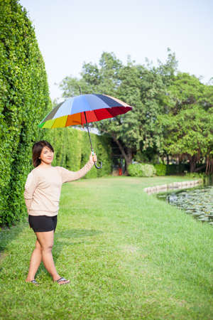 Asian woman holding an umbrella in the park. Stood on the lawn beside a tree. photo