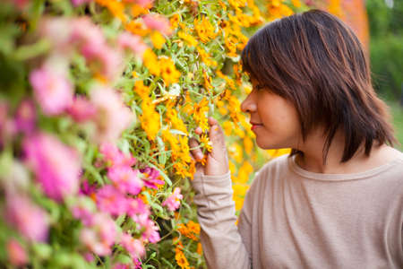 Portrait Asian woman standing near yellow flowers. And smell the flowers photo