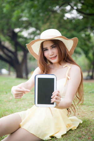 Asian women filed tablet and pointing to the tablet. She sitting on lawn in the park. photo