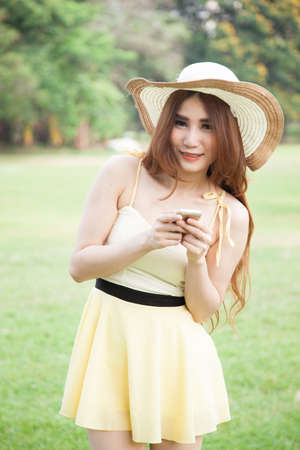 Asian woman smiling and holding a mobile phone. In the park photo