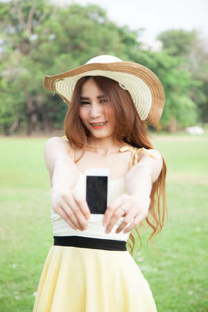 Asian woman smiling and handing a mobile phone.Smiling happy and Relax. photo