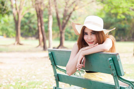 Asian women sitting on a bench in the park. She was wearing a hat and holding mobile phone photo