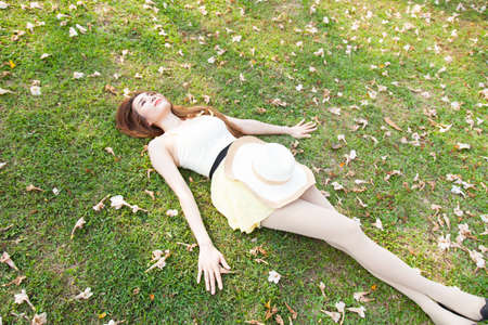 Asian woman lying on the grass in the park. Relax during weekends.