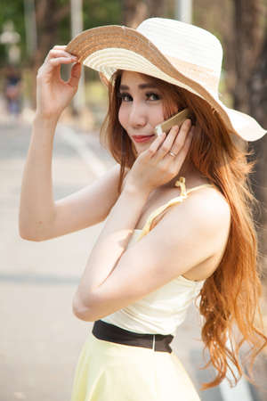 Portrait asian woman portrait Portrait hat. Talking on mobile phone In the park photo
