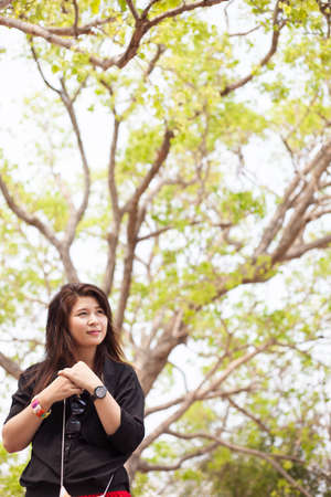 Asian women black shirt standing under a tree. Looking forward photo