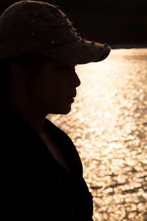 sop: Backlit silhouette of a woman wearing a hat. Sop freckled sunlight reflecting off the surface of the sea in the evening.