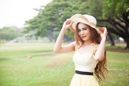 Woman wearing a hat at the park. Bright and tranquil environment of the park. photo