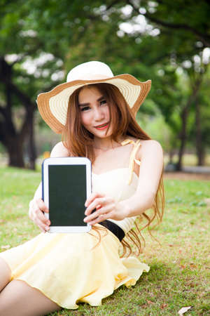 Women filed the tablet. Sitting on the grass in the park. photo