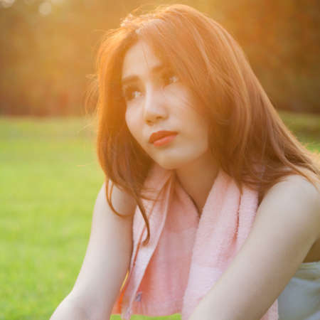 Woman sitting on lawn in park., In the evening, with the sun warm. photo