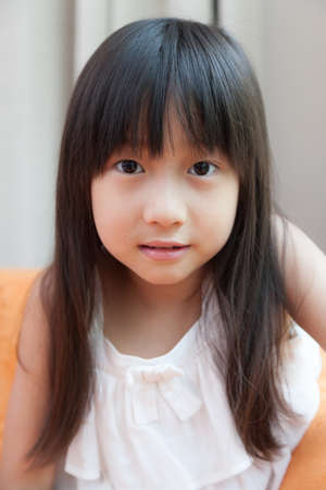 Child Asian woman with long black hair. Sitting on the sofa at home photo