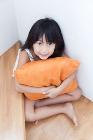 Girl sitting hugging pillow orange. On the ladder inside the house photo