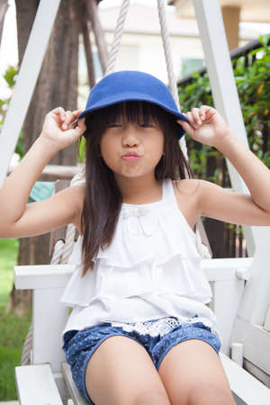 girl sitting on a swing. hand holding blue hat. Smiling and laughing photo