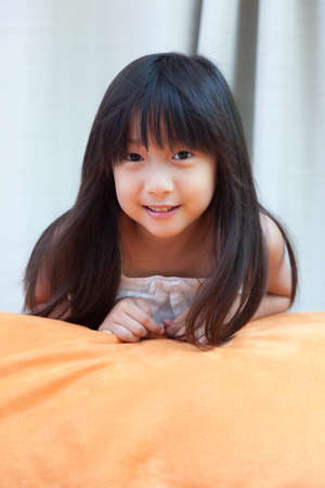 girl with long black hair Asia girl with orange pillows. photo