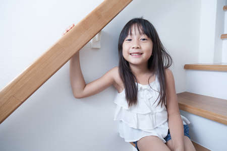 Child girl sitting on the ladder. And smiling happily. photo