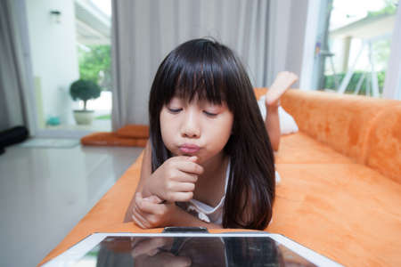 Girl playing with tablet. Played on the orange sofa. Gestures are funny and happy. photo