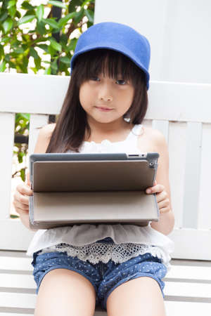 Girl playing with tablet on bench. girl with long black hair wearing blue hat. photo