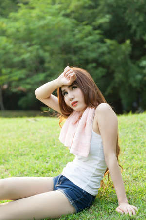 Woman sitting tired after jogging. Located on the lawn in the park. photo
