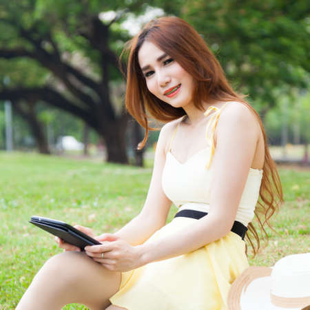 Woman sitting on lawn Hand holding tablet and thinking. photo