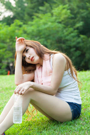 tried: Woman sitting tired and drinking water after exercise. Within the lawn of park.