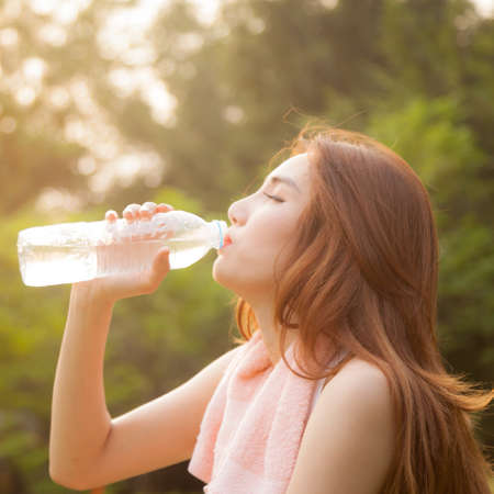Woman sitting tired and drinking water after exercise. Within the lawn of park. photo