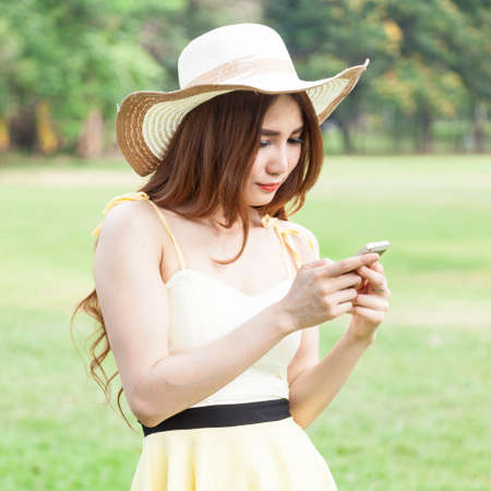 Woman playing smart phone While on the lawn in the park. photo