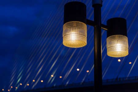 streetlamp: Lighting of lamps at night. In the background is the bridge over the river during the night opened fire.