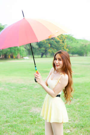 strongest: Woman with umbrella standing on the lawn. In the park during the day, the sun is strongest.