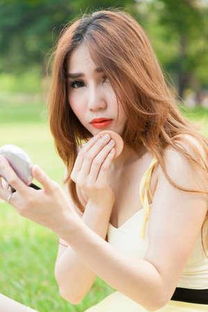 Asian woman makeup Womans long hair makeup powder on the lawn. photo