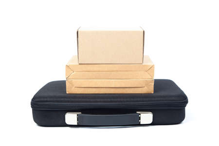 Many brown paper box on a black briefcase in studio white isolated background. photo