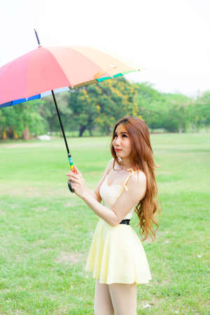 the strongest: Woman with umbrella standing on the lawn. In the park during the day, the sun is strongest.