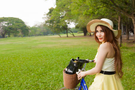 Woman riding a bicycle. Woman with hat riding a bicycle in the park. photo