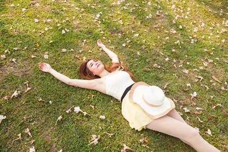 Vrouw liggend op het gras. Het gras bedekt met afgevallen bloemen.